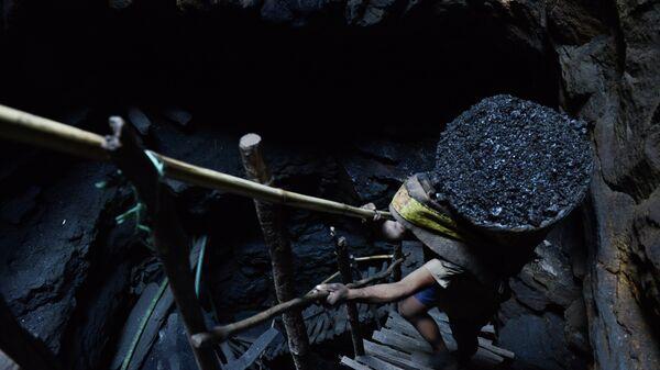 A miner slowly carries a heavy load of wet coal - Sputnik International