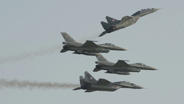 Two Polish Air Force Russian made Mig 29's fly above and below two Polish Air Force U.S. made F-16's fighter jets during the Air Show in Radom, Poland, Saturday, Aug. 27, 2011 - Sputnik International