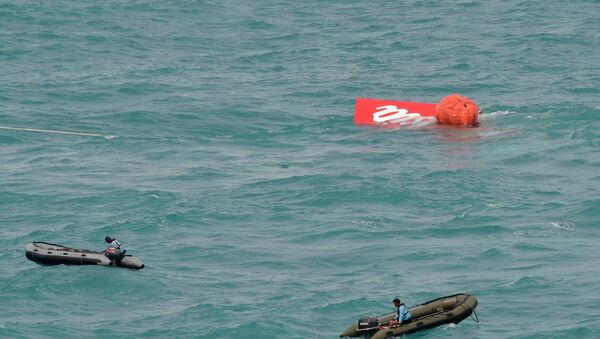 Part of the tail of AirAsia QZ8501 floats on the surface after being lifted as Indonesian navy divers conduct search operations for the black box flight recorders and passengers and crew of the aircraft, in the Java Sea January 10, 2015. - Sputnik International