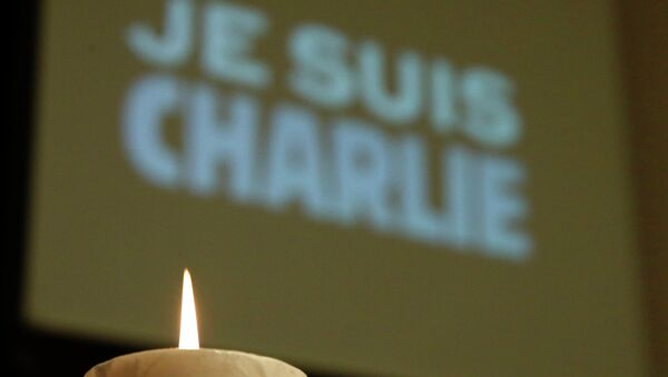 A candle is pictured in front of a Je suis Charlie (I am Charlie) sign - Sputnik International