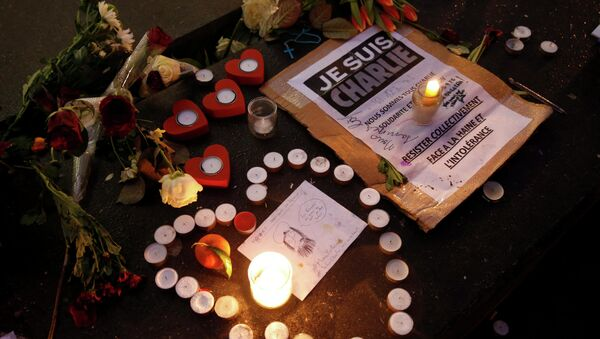 Candles form a heart, near a placard with the message, I am Charlie as people continue to pay tribute to the shooting victims on Wednesday at the satirical weekly Charlie Hebdo, at the Republique square in Paris - Sputnik International