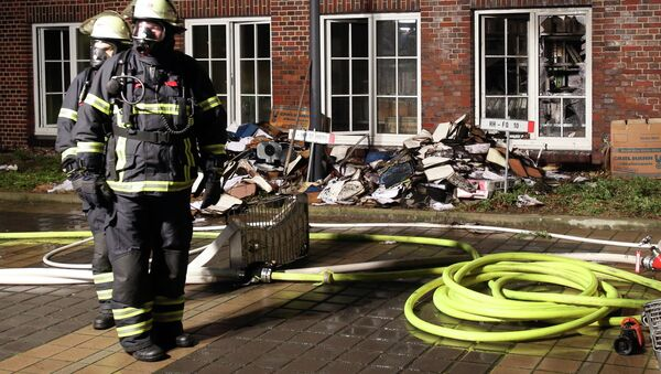 Firefighters stand outside the building of the 'Hamburger Morgenpost' in Hamburg, northern Germany, Sunday morning, Jan. 11, 2015. - Sputnik International