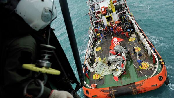 The tail of AirAsia QZ8501 passenger plane is seen on the deck of the rescue ship Crest Onyx from an Indonesian Super Puma military helicopter after it was lifted from the sea bed, south of Pangkalan Bun, Central Kalimantan - Sputnik International