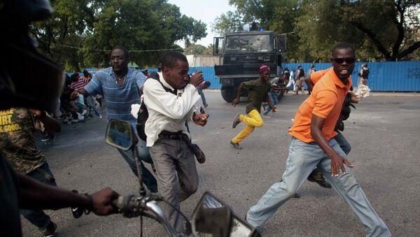Demonstrators run during a protest demanding the resignation of President Michel Martelly in Port-au-Prince - Sputnik International