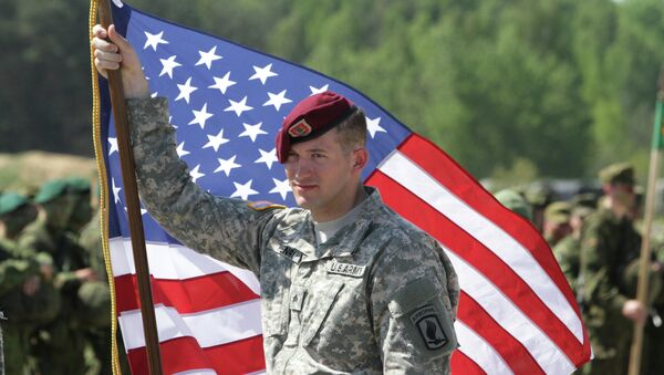 A paratrooper of the 173rd Airborne Brigade of the US Army in Europe holds his country's flag after the final operation of the exercise Black Arrow 2014 in Rukla, Lithuania - Sputnik International