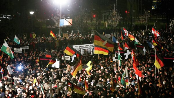 Supporters of anti-immigration movement Patriotic Europeans Against the Islamisation of the West (PEGIDA) hold flags during a demonstration in Dresden - Sputnik International