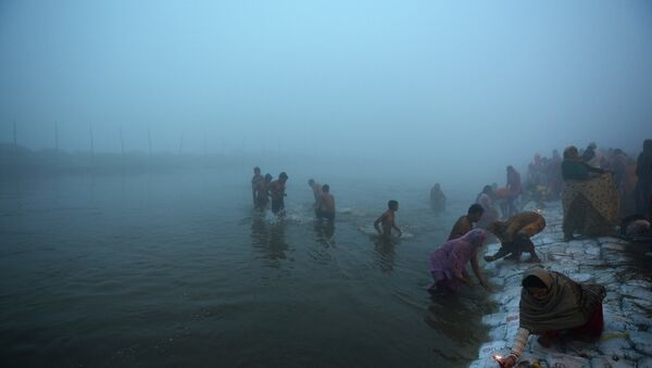 Indian Hindu devotees take a holy dip for the Makar Sankranti festival during the annual Magh Mela gathering at Sangam, the confluence of the rivers Ganges, Yamuna and the mythical Saraswati, during a cold and foggy morning in Allahabad on January 14, 2015 - Sputnik International