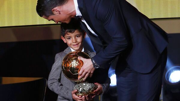 Real Madrid's Cristiano Ronaldo of Portugal, stands with his son Cristiano Ronaldo Jr, after winning the FIFA Ballon d'Or 2014 during the soccer awards ceremony at the Kongresshaus in Zurich January 12, 2015 - Sputnik International