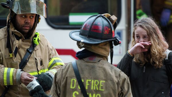 Firefighters speak with a victim after passengers on the Metro (subway) service were injured when smoke filled the L'Enfant Plaza station during the evening rush hour - Sputnik International