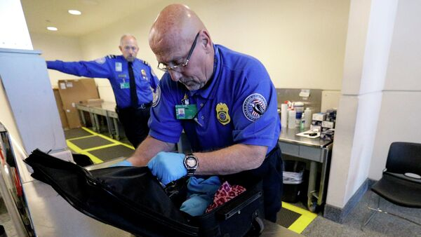 A TSA agent checks a bag at a security checkpoint area at Midway International Airport, Friday, Nov. 21, 2014, in Chicago - Sputnik International