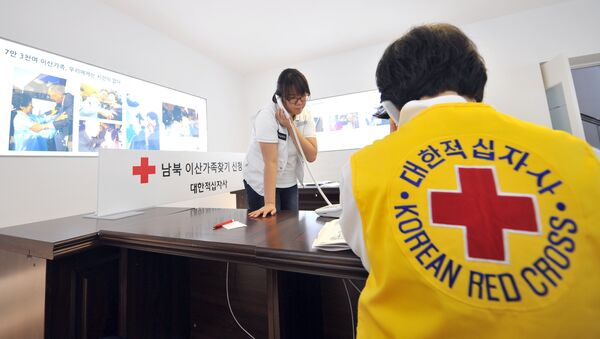 South Korean Red Cross officials talk on the phones as they receive applications for an expected inter-Korean family reunion programme - Sputnik International
