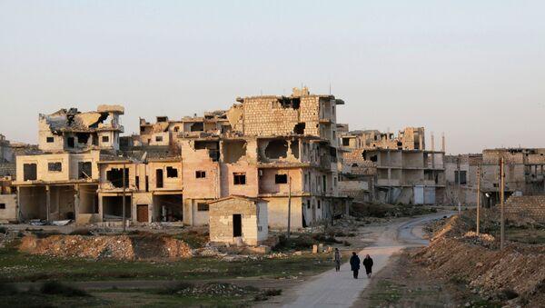 Residents walk near damaged buildings in Maaret al-Naaman town in Idlib province January 14, 2015 - Sputnik International