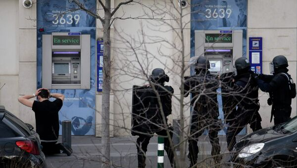 A suspect in a hostage taking situation is detained by members of special French RAID forces outside the post offices in Colombes outside Paris, January 16, 2015 - Sputnik International