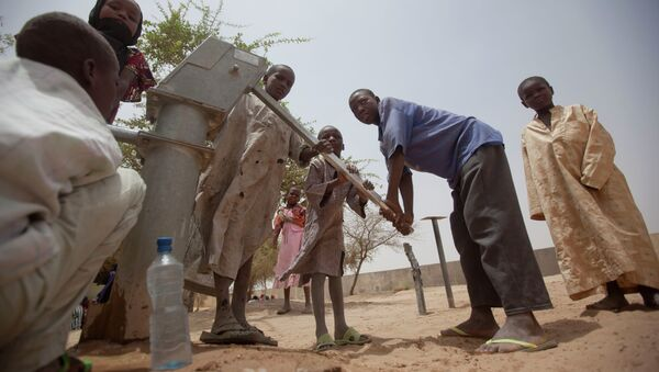 Children pump water to drink from a well in the courtyard of a walk-in feeding center in Dibinindji, a desert village in the Sahel belt of Chad, Wednesday, April 18, 2012 - Sputnik International