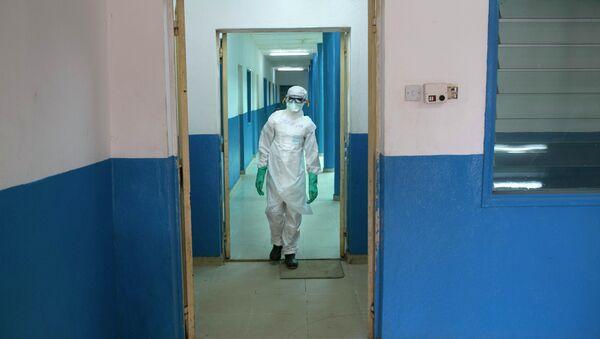 A health worker in protective gear walks inside a Red Cross facility in the town of Koidu, Kono district in Eastern Sierra Leone December 19, 2014 - Sputnik International
