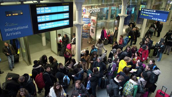 Passengers wait in the long queues at Saint Pancras International station in London - Sputnik International