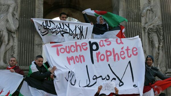 French Muslim youths hold a Islamic flag (top) and a banner reading Do not touch my prophet, anything but the Messenger of Allah as they gather in central Paris January 18, 2015 - Sputnik International