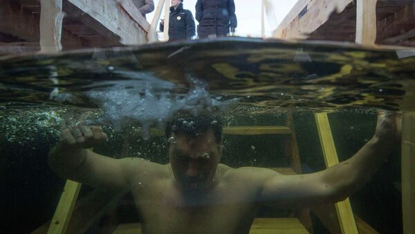 A man immerses himself in an ice hole in the Moskva river during celebrations for Russian Orthodox Epiphany on the outskirts of Moscow - Sputnik International