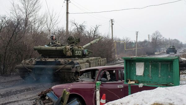 A man rides a Ukrainian tanks past a damaged vehicle in the village of Tonenke, some 5 kilometers from the Donetsk airport - Sputnik International