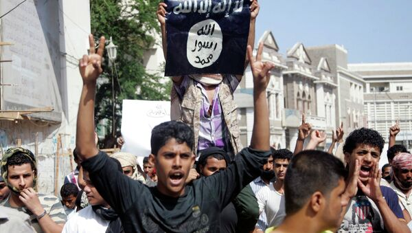 A protester holds up the flag of the Islamic State - Sputnik International