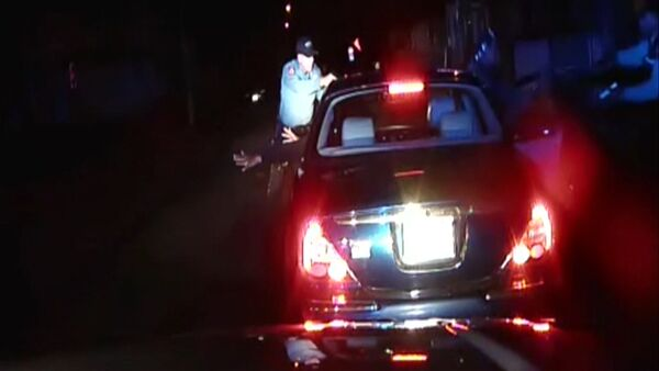 In this frame grab from an officer's dashboard camera taken Dec. 30, 2014, and provided by the Bridgeton, N..J. Police Department, police officers Braheme Days and Roger Worley stand near a car they pulled over for running a stop sign in Bridgeton - Sputnik International
