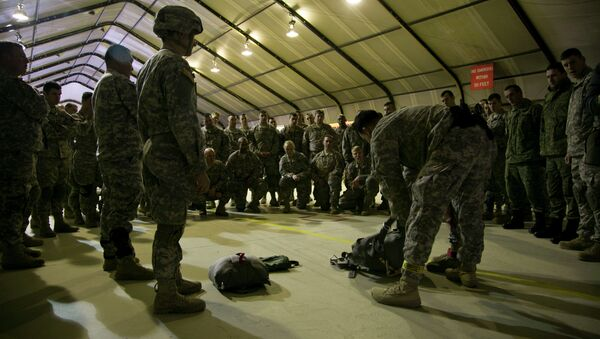 US Army soldiers of the 4th Infantry Brigade, Combat team (Airborne) 25th Infantry Division, part of the NATO-led peacekeeping mission in Kosovo listen to jump master how to prepare their gear for a parachute training exercise in US military base Camp Bondsteel, near the village of Sojeve in Kosovo on Sunday, Dec. 21, 2014 - Sputnik International