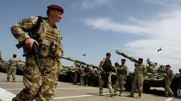 A British army soldier walks past Iraqi army tanks during a training mission in Latifiyah, 30 kilometers (20 miles) south of Baghdad, Iraq - Sputnik International