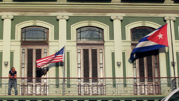 A man stands near the national flags of the U.S. and Cuba (R) on the balcony of a hotel being used by the first U.S. congressional delegation to Cuba since the change of policy announced by U.S. President Barack Obama on December 17, in Havana - Sputnik International