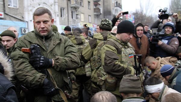 Leader of the self-declared Donetsk People's Republic Alexander Zakharchenko (L) stands next to kneeling captive Ukrainian soldiers at a bus stop where 13 people were killed in a trolleybus shelling in Donetsk, eastern Ukraine, on January 22, 2015 - Sputnik International