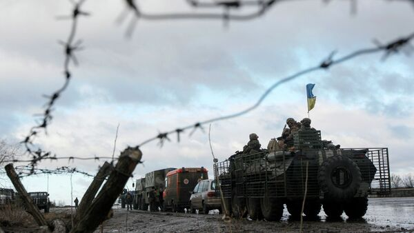 A Ukrainian military convoy is pictured through a barbed wire fence at a military base in the town of Kramatorsk, eastern Ukraine - Sputnik International
