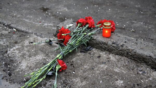A candle and flowers are layed at a bus stop where 13 people were killed in a trolleybus shelling in Donetsk, eastern Ukraine, on January 22, 2015 - Sputnik International