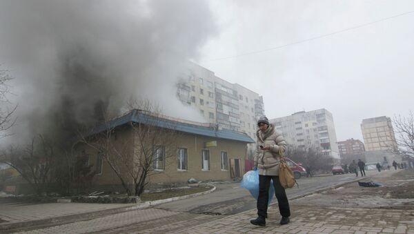 A woman resident passes by a burning house in Mariupol, Ukraine, Saturday, Jan. 24, 2015 - Sputnik International