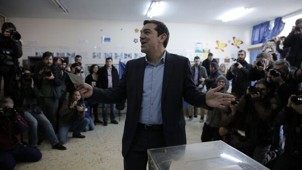 Alexis Tsipras, leader of Greece's Syriza left-wing main opposition party surrounded by photographers reacts as he casts his vote at a polling station in Athens, Sunday, Jan. 25, 2015 - Sputnik International