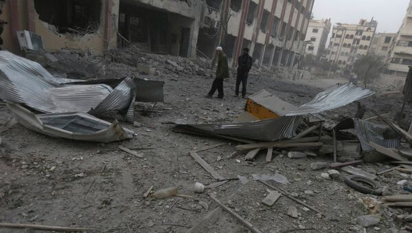 Residents inspect a damaged site after what activists said were air strikes by forces loyal to Syria's President Bashar al-Assad in Douma eastern Al-Ghouta, near Damascus January 25, 2015 - Sputnik International