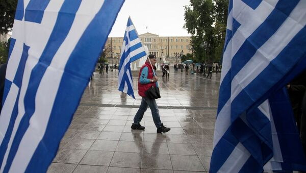 A man holding a Greek flag walks on central Syntagma square as the parliament is seen in the background, in Athens January 24, 2015 - Sputnik International