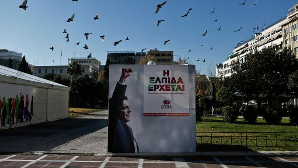 A flock of pigeons flies over a banner with an image of opposition leader and head of radical leftist Syriza party Alexis Tsipras at the party's pre-election kiosk in Athens January 15, 2015. - Sputnik International