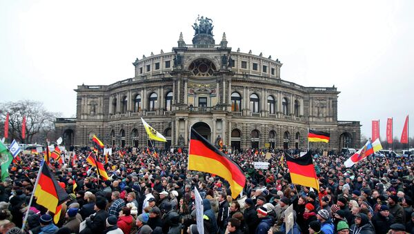 Members of the movement of Patriotic Europeans Against the Islamisation of the West (PEGIDA) hold flags and banners during a PEGIDA demonstration march in Dresden - Sputnik International