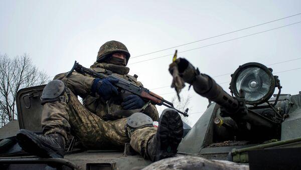 A Ukrainian serviceman rides on APC - Sputnik International