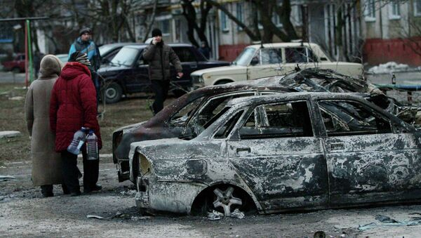 People look at burned out cars as they walk along a street in the southern Ukrainian city of Mariupol - Sputnik International