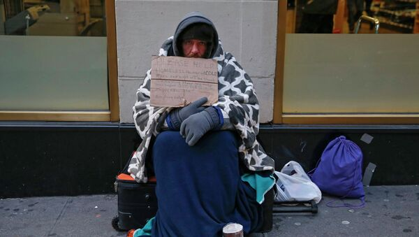 A man holding up a sign stating he is 'homeless, hungry and cold' sits along 7th avenue in New York  - Sputnik International