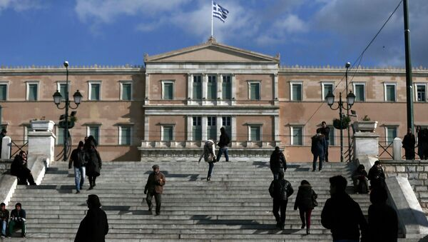 People make their way in central Syntagma Square as the parliament building is pictured in the background in Athens - Sputnik International