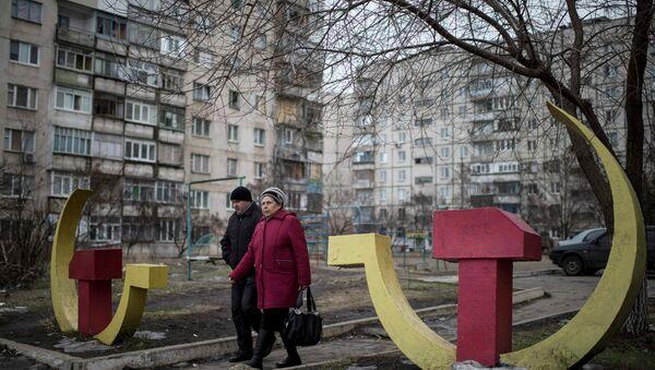 Local residents walk past Soviet-era hammer and sickle sculptures outside an apartment building damaged after Saturday's shellingin Mariupol, Ukraine - Sputnik International