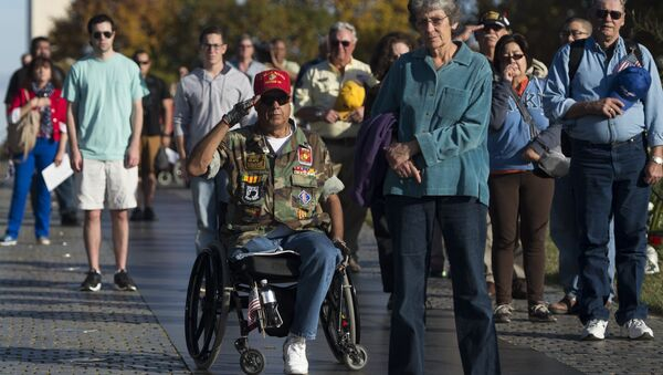 Vietnam War veteran Joe Caballero (C) salutes during the playing of Taps at the Vietnam Veterans Memorial wall on the National Mall in Washington, DC - Sputnik International