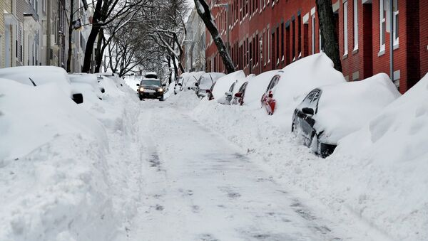 A car makes its way down a street filled with snowed-in vehicles in Boston's Charlestown section, Wednesday, Jan. 28, 2015 one day after a blizzard dumped about two feet of snow in the city - Sputnik International
