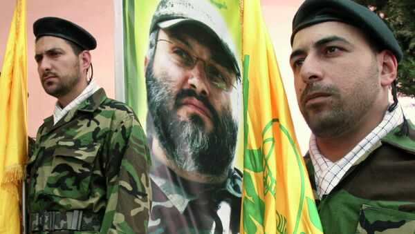 Hezbollah members stand guard in front of a picture of assassinated Hezbollah top commander Imad Mughniyeh - Sputnik International