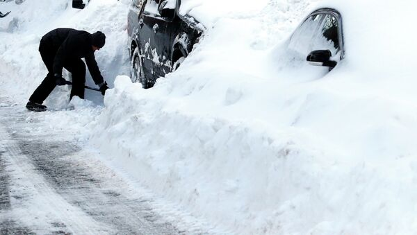 Max Gomez shovels his vehicle out at his home in Boston's Charlestown section, Wednesday, Jan. 28, 2015, one day after a blizzard dumped about two feet of snow in the city - Sputnik International