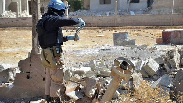 Member of UN investigation team taking samples of sands near a part of a missile that is likely to be one of the chemical rockets according to activists, in Damascus countryside of Ain Terma, Syria - Sputnik International