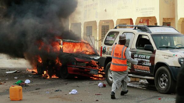 A man rushes towards a vehicle next to a burning car at the scene of a bomb explosion in Gombe - Sputnik International