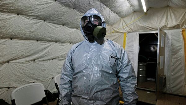 A marine officer of the Cape Ray, a ship equipped to neutralize Syrian chemicals, shows a chemical protection suit to reporters - Sputnik International