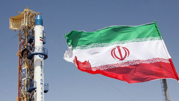 Iranian flag fluttering in front of Iran's Safir Omid rocket, which is capable of carrying a satellite into orbit, before it's launch in a space station at an undisclosed location in the Islamic republic - Sputnik International